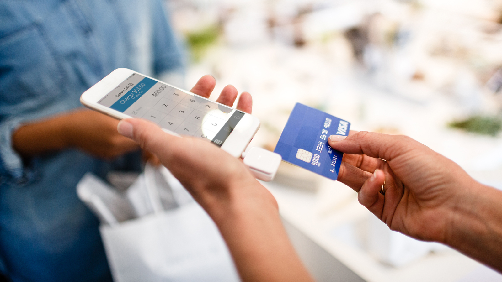 Merchant using a mobile phone to complete a transaction
